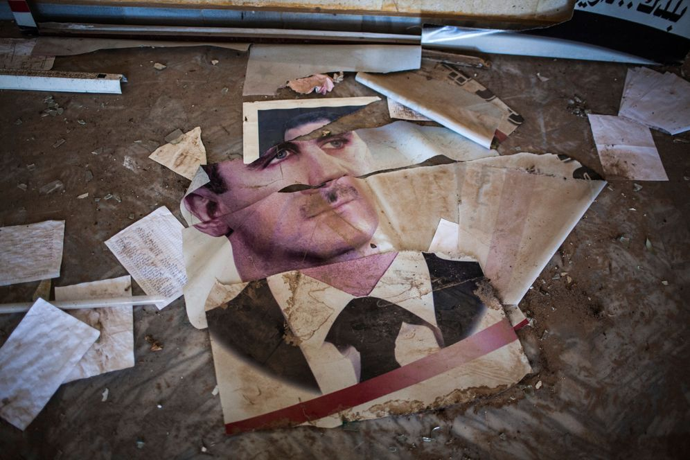 A torn portrait of Syrian President Bashar Assad on the floor of a building in Raqqa in 2013