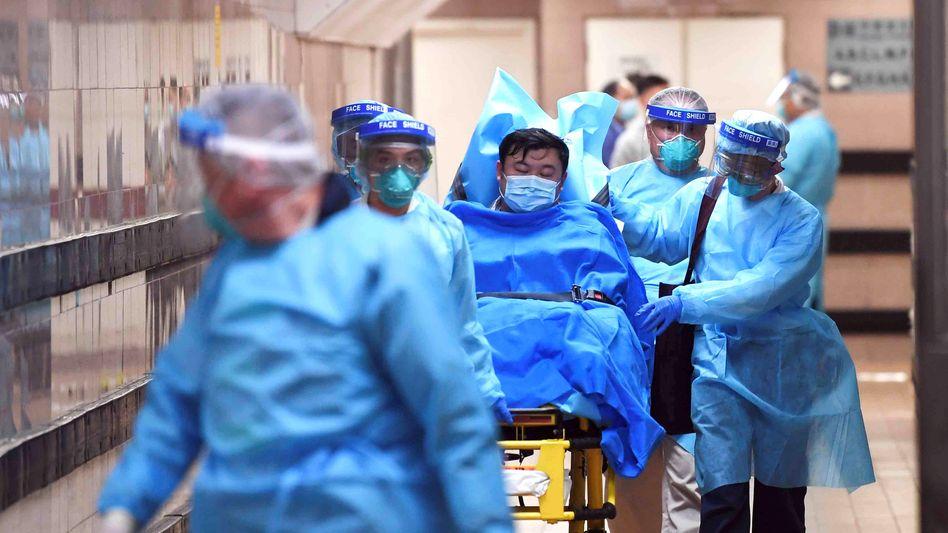 Krankenhausmitarbeiter mit einem wahrscheinlich mit dem Coronavirus Infizierten im Queen Elizabeth Hospital in Hong Kong