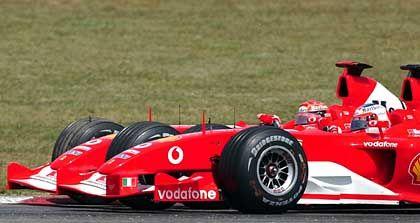 Gleiche Höhe: Verbissen kämpfen die beiden Ferrari-Piloten Michael Schumacher (l.) und Rubens Barrichello nach dem Start um die beste Position