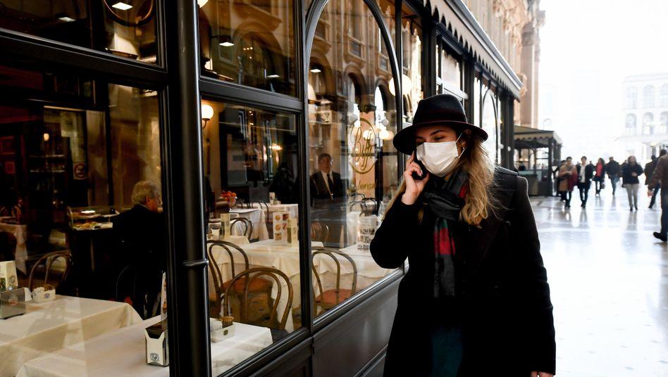 Ausgehen in Zeiten des Virus: Passantin vor einem Restaurant in Mailand