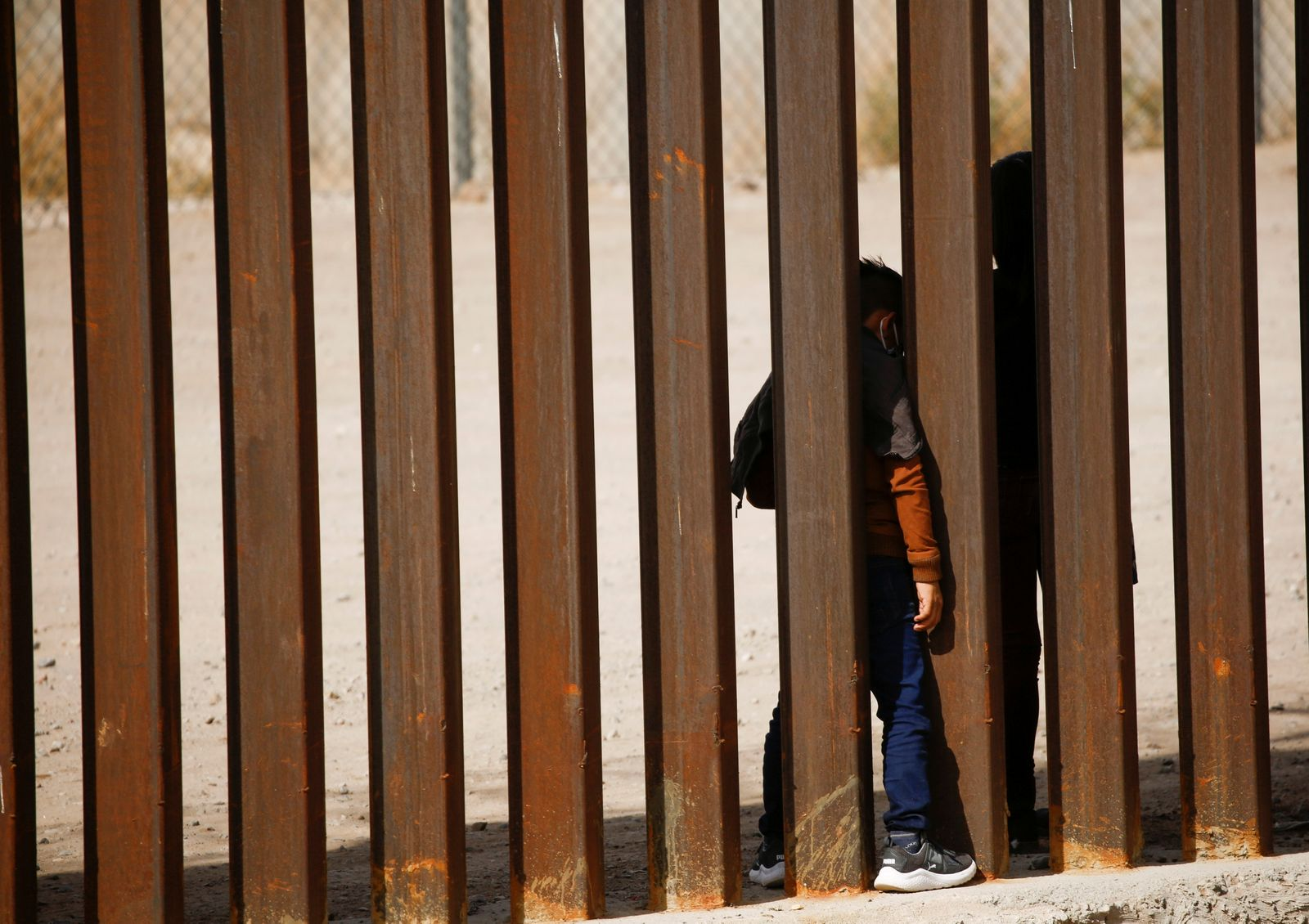 Migrant child is seen through the border wall after crossing the Rio Bravo river to turn himself with his family in to U.S. Border Patrol agents to request for asylum in El Paso, Texas