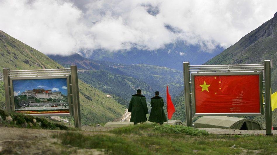 Chinesische Militärs neben ihrer Landesfahne nahe dem indischen Bundesstaat Sikkim