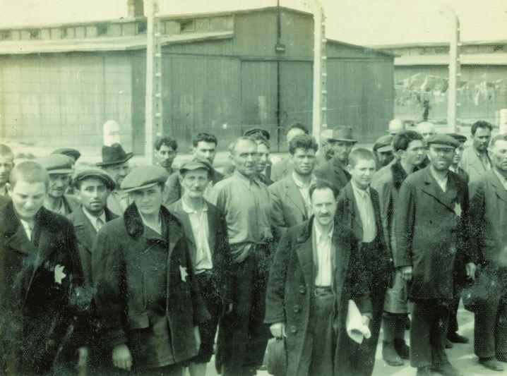 Im Hintergrund stehen Häftlinge, die wegen der Ankunft des Transports den abgezäunten Lagerbereich nicht verlassen durften.