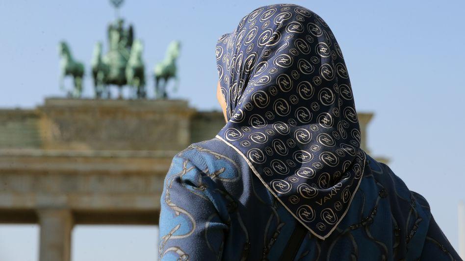 """Frau mit Kopftuch vor dem Brandenburger Tor (Archiv): """"Feindbild Muslim in der öffentlichen Wahrnehmung verankert"""""""