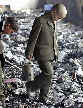 Ein Junge sucht nach den Plündereien im Schutt nach Brauchbarem