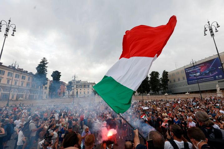 Demonstranten zünden bei einer Demonstration gegen den geplanten »grünen Pass« einen Bengalo