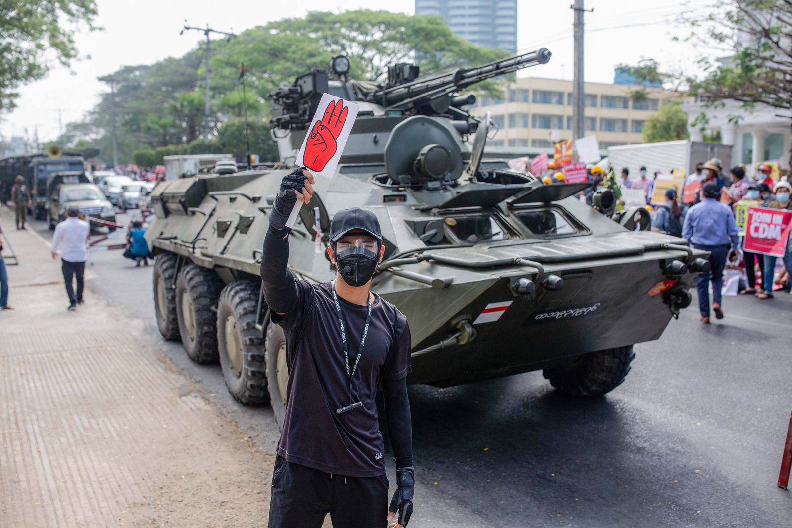 February 15, 2021, Yangon, Myanmar: A protester holds a placard with a three-finger salute in front of a military tank