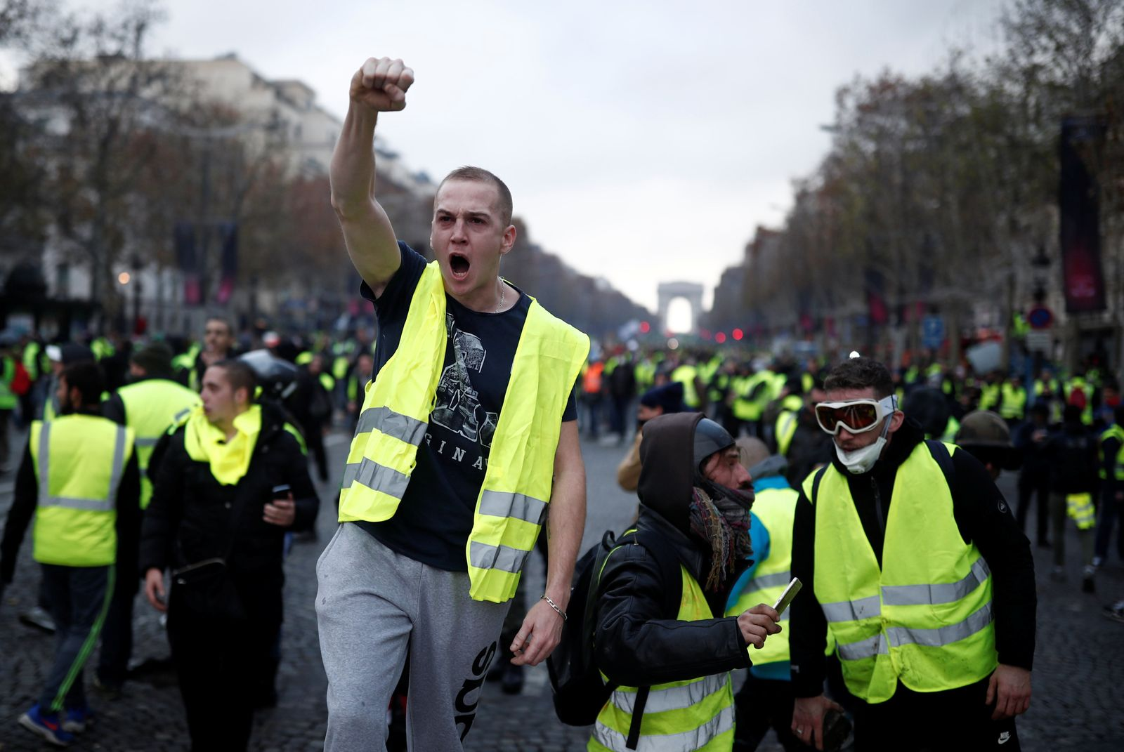 A protester wearing yellow vest, a symbol of a French drivers' protest against higher fuel prices, gestures during clashes on the Champs-Elysees in Paris