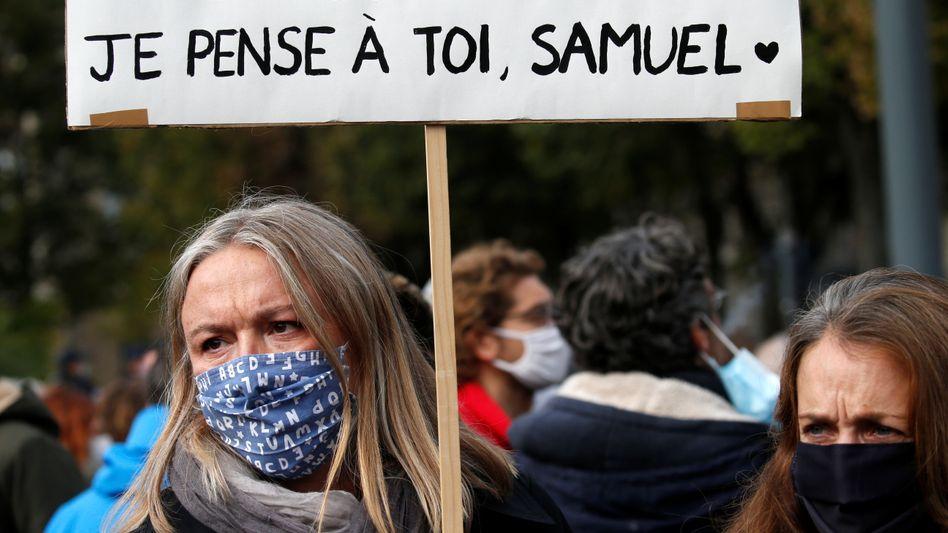 """""""Ich bin Lehrerin. Ich denke an Dich, Samuel"""", steht auf Poster dieser Demonstrantin in Lille"""