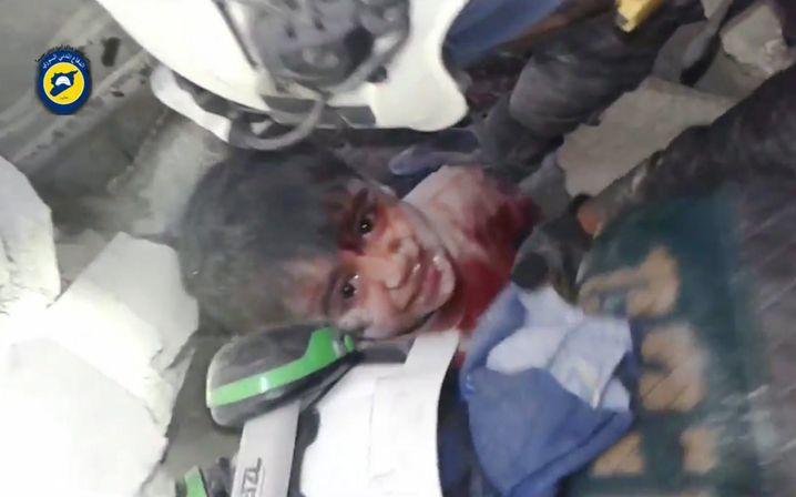 Weißhelme retten ein Kind aus Trümmern in Aleppo