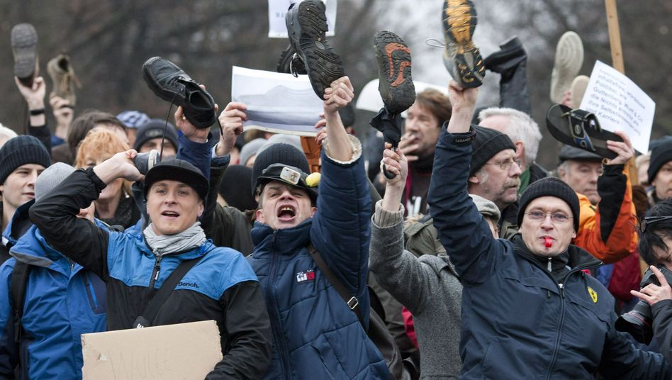 Demonstrators wave shoes as a sign of disrespect during a demonstration against German President Christian Wulff in front of his official residence in Berlin on Saturday.