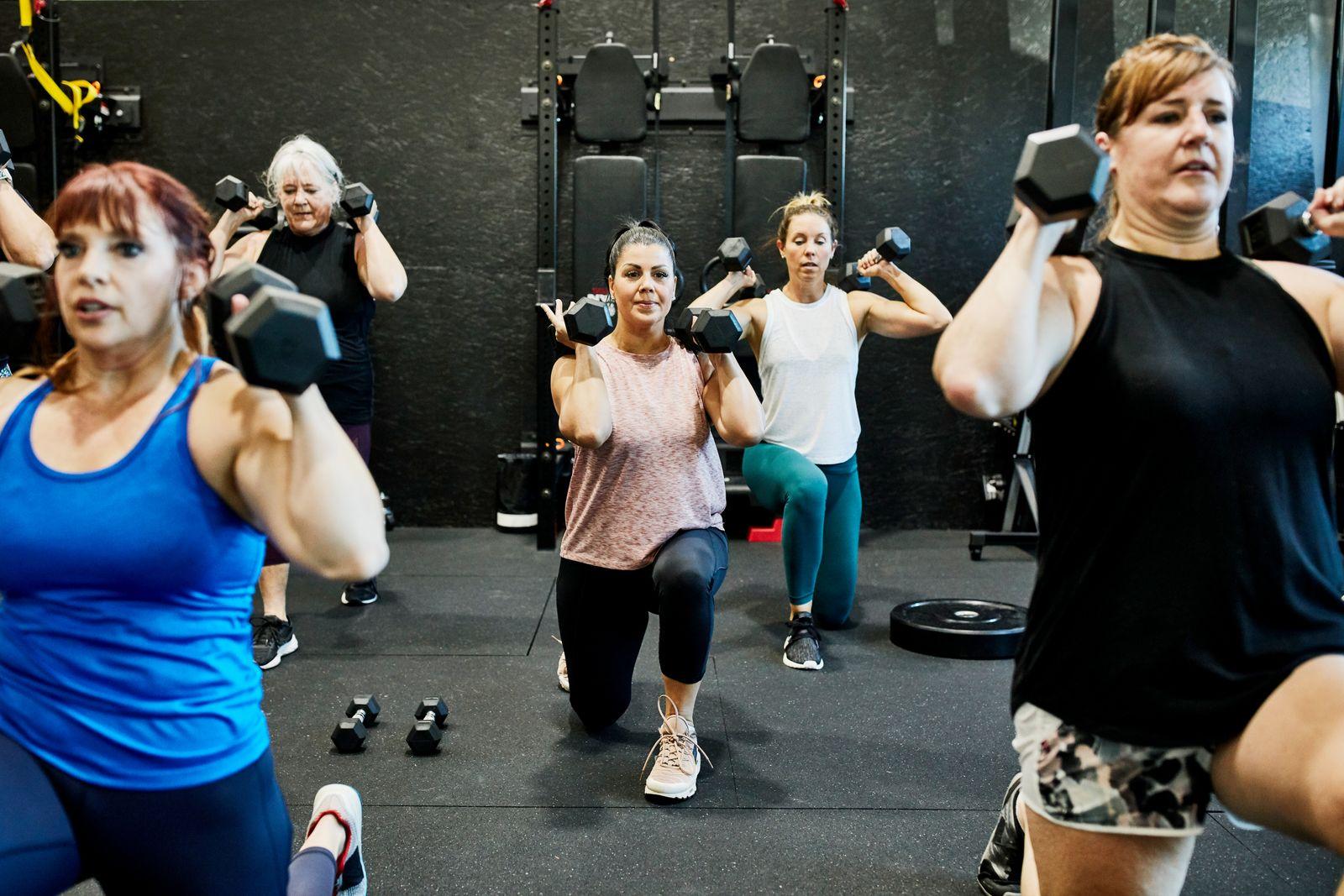 Womens fitness class doing dumbbell lunges in gym