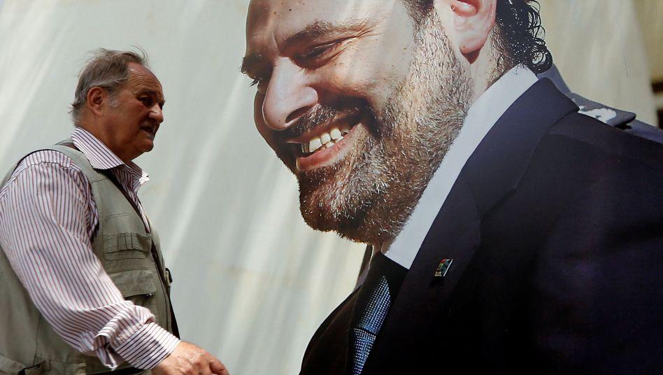 Mann vor Hariri-Wahlplakat