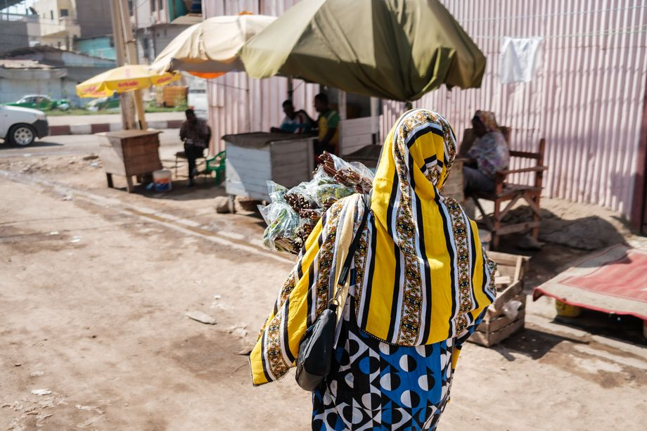 Vendor Zainaba A. on the way to her stand, arms full of khat.