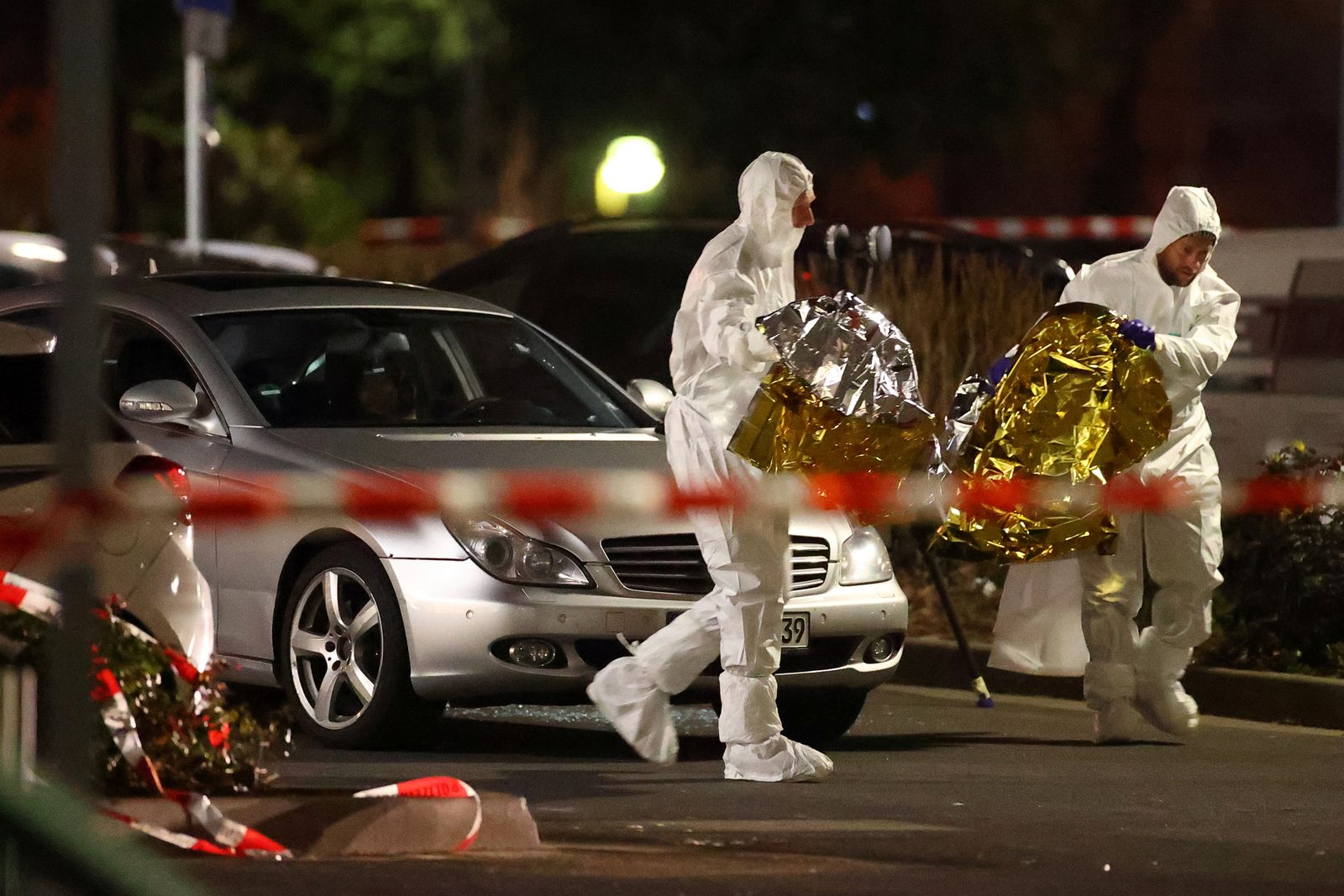 A body is seen in a damaged car as forensic experts work after a shooting in Hanau near Frankfurt