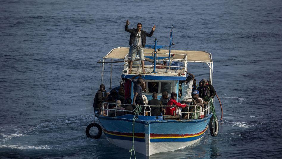 Migrant an Bord eines Bootes winkt in Richtung eines spanischen Rettungsschiffs (Archivbild)