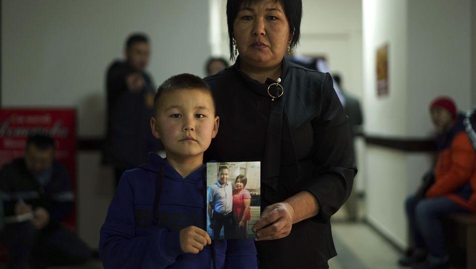 Sala Jimobai und ihr Sohn halten ein Bild von ihrem Vater und Ehemann, Dakey Zhunishan, der interniert worden sein soll