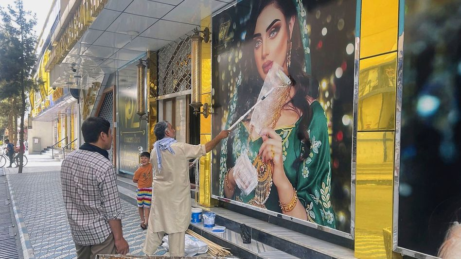 A man paints over an image of a woman at a beauty salon in Kabul