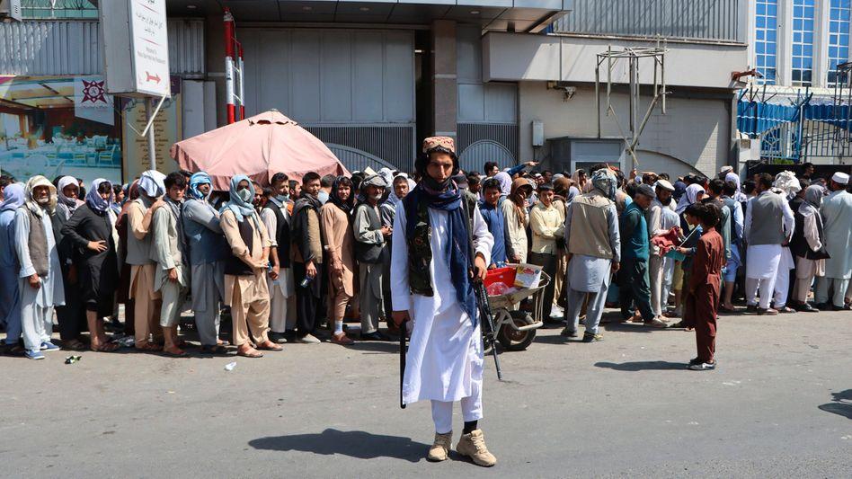 Ein Taliban bewacht Afghanen, die sich zum Geldabheben vor einer Bankfiliale anstellen