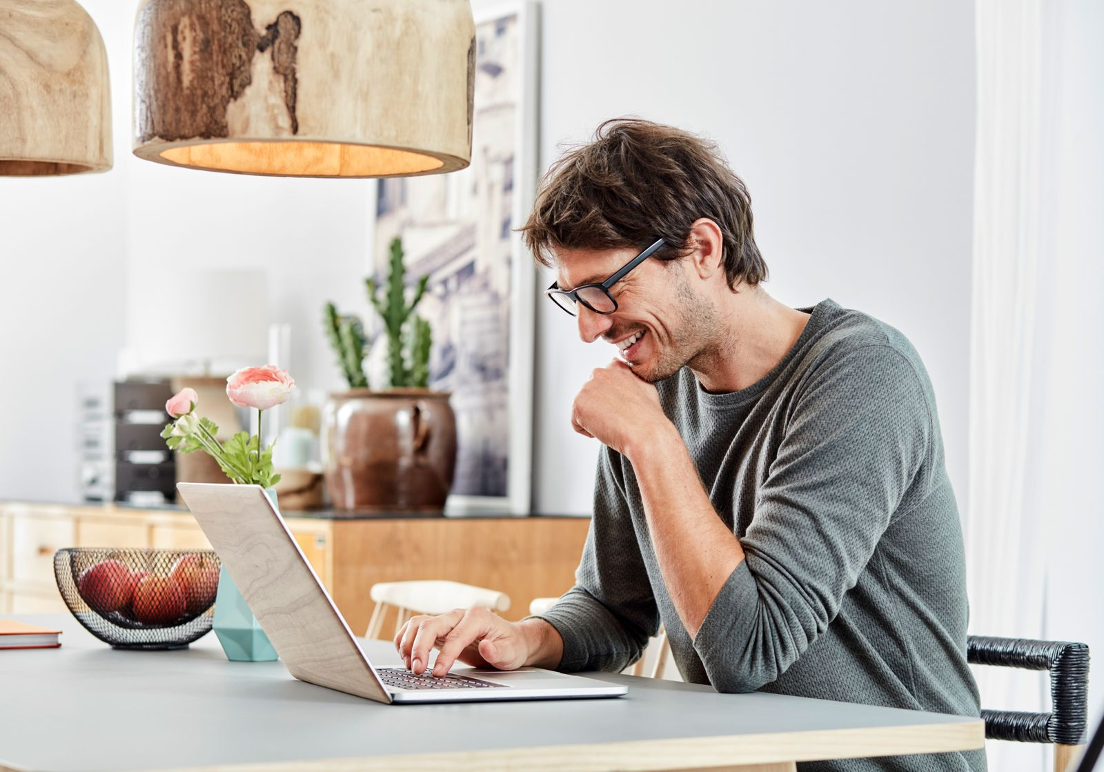 Smiling man using laptop on table at home