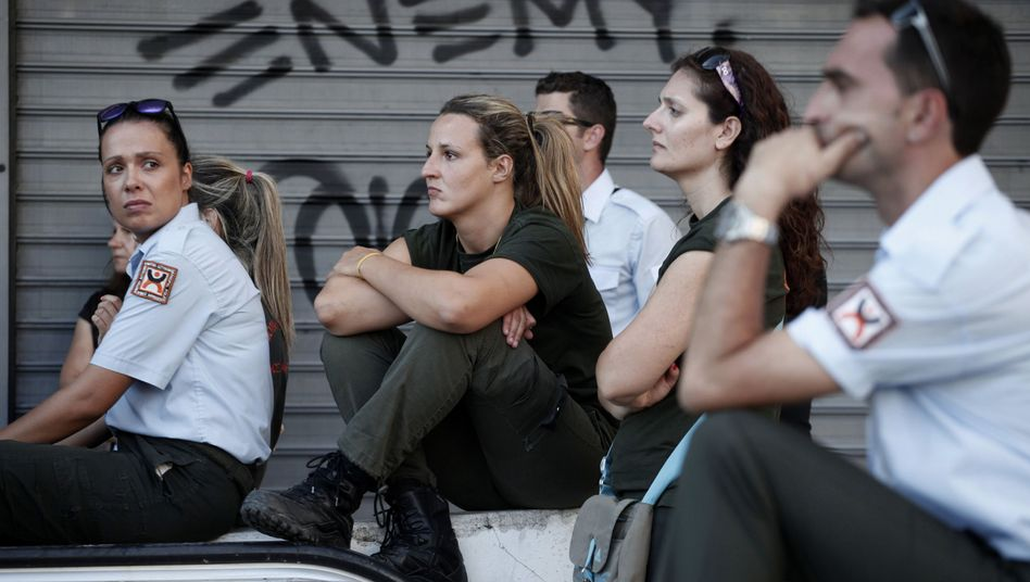 Municipal police officers react after learning on Monday that Athens plans to place 12,500 public sector workers on administrative leave.