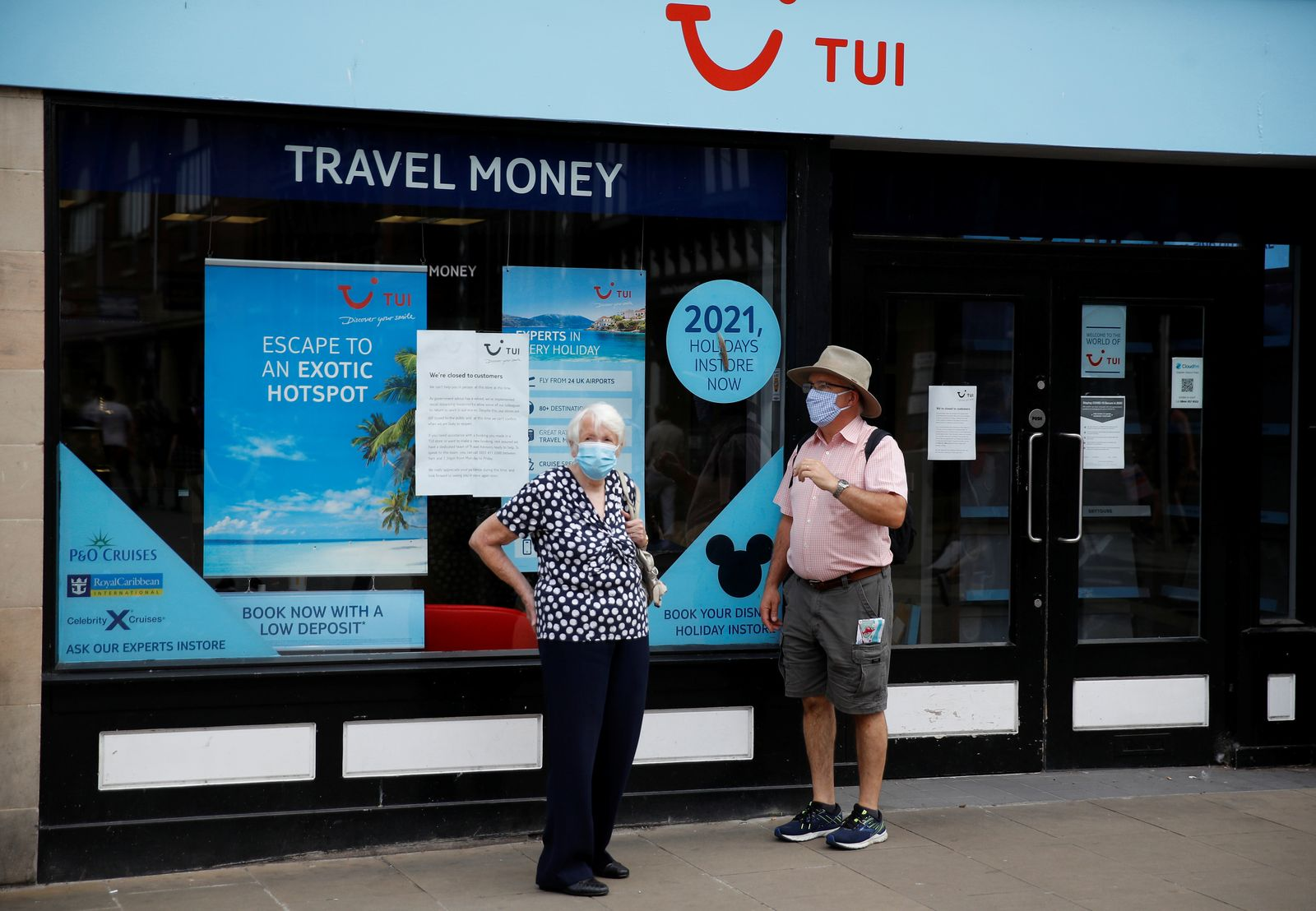 People wear face coverings as they stand outside a Tui travel agents shop following the outbreak of the coronavirus disease (COVID-19) in Chester, Britain