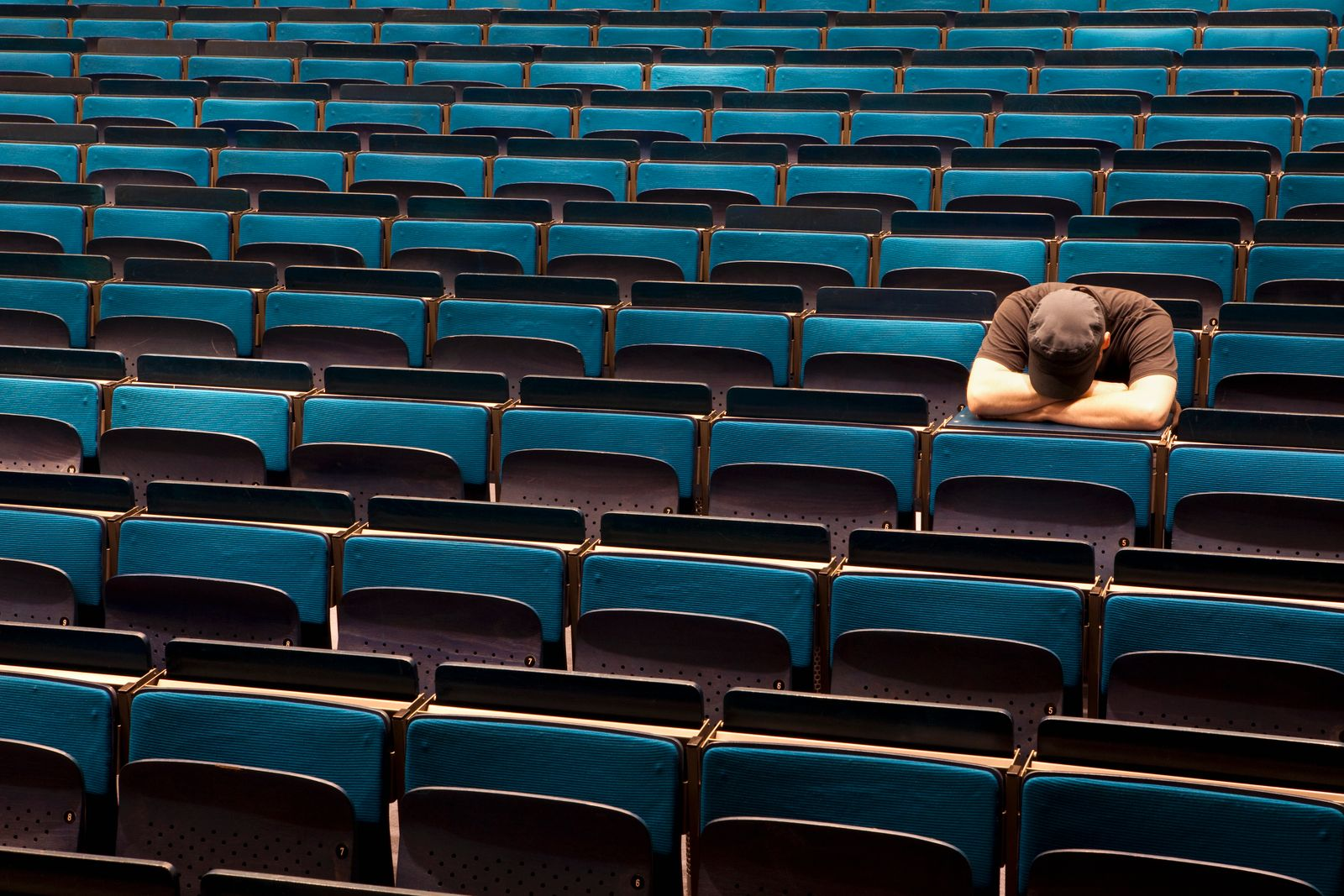 A man sitting in an auditorium with his head resting in his arms
