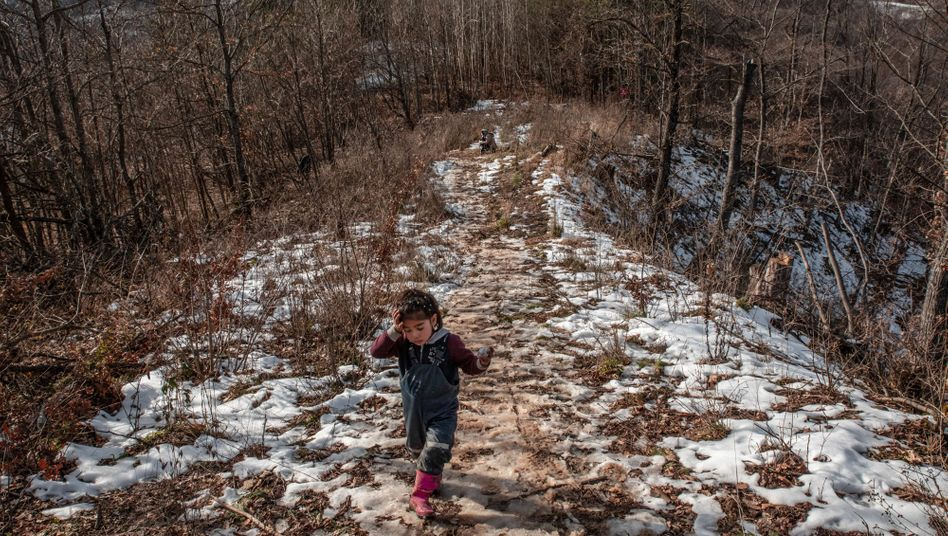 An Afghan girl runs through slush near the border between Bosnia-Herzegovina and Croatia.