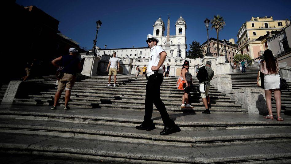 Ein Polizist vertreibt Touristen mit einer Trillerpfeife von der Spanischen Treppe