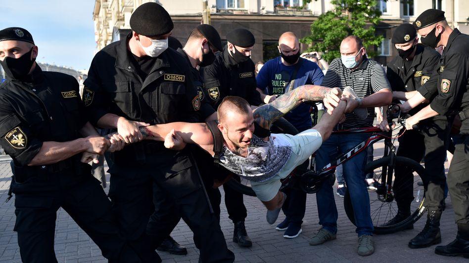 Sicherheitskräfte tragen einen Demonstranten in Minsk weg