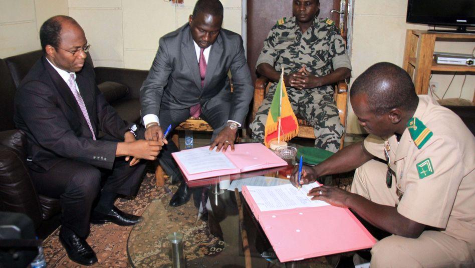 Sanogo (r.) unterschreibt das Abkommen zur Machtübergabe: Wahlen binnen 40 Tagen