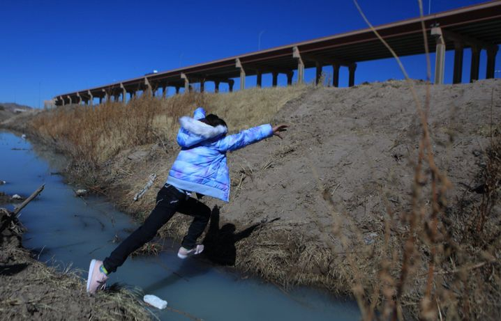 A boy from Central America jumps across a stream on the Rio Grande at the Mexican-U.S. border in Ciudad Juárez.