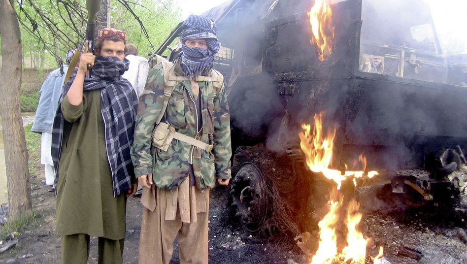 Taliban insurgents pose in front of a burning German military vehicle in Chahar Dara district, on the day after three German soldiers were killed in an ambush.