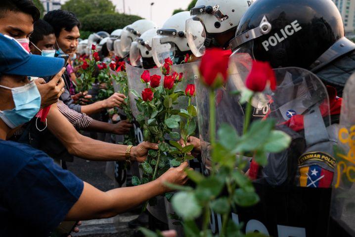 Symbol des Friedens: Protestierende überreichen Bereitschaftspolizisten rote Rosen