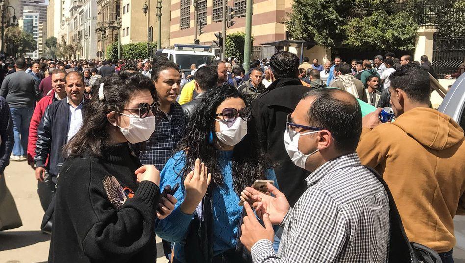 Passanten mit Schutzmasken in Kairo: Der Kampf gegen das Virus beginnt nur langsam