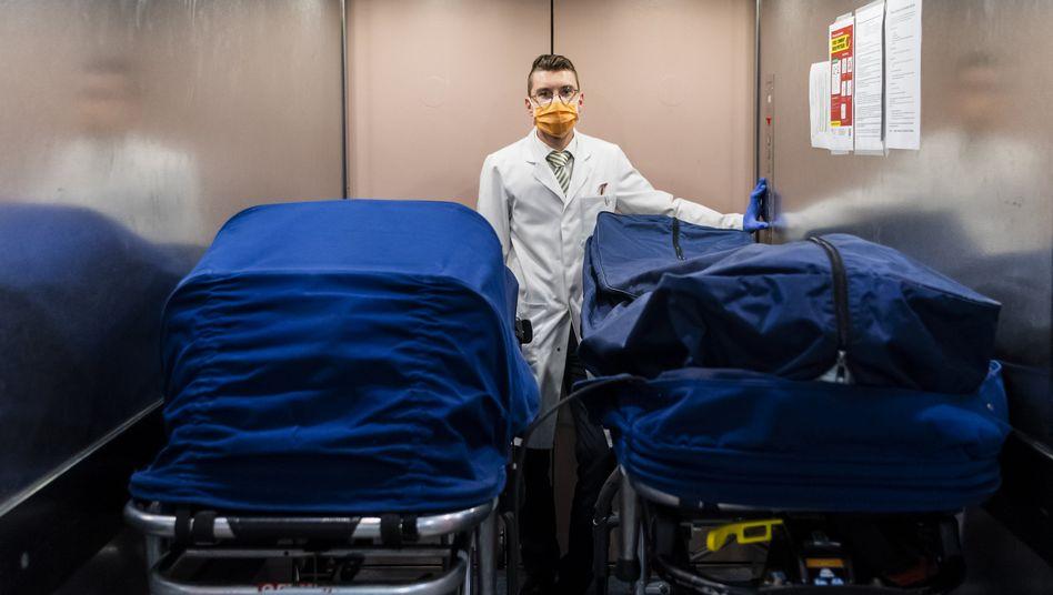 Ein Mitarbeiter eines Bestattungsunternehmenstransportiert die Leichen von zwei Covid-Opfern, Lausanne, Schweiz
