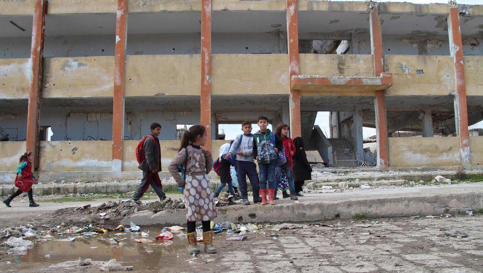 Syrische Kinder auf einem zerstörten Schulhof in Idlib