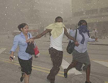 Menschen bringen sich vor herabfallenden Trümmerteilen in Sicherheit