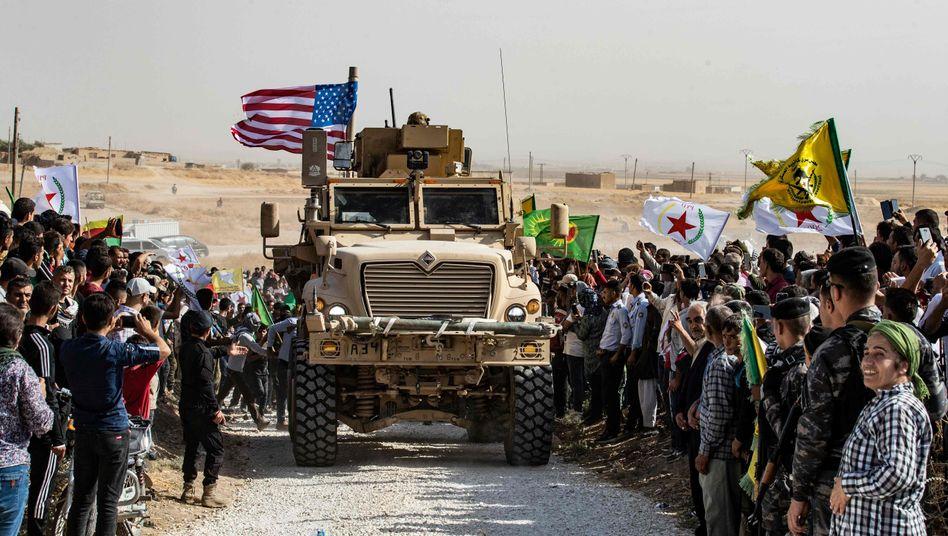 Gepanzerter US-Truck und kurdische Demonstranten nahe der syrischen Grenze