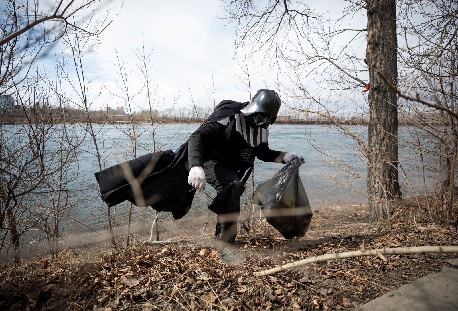 A volunteer dressed as the Star Wars character Darth Vader picks up trash during a street cleaning event in Irkutsk