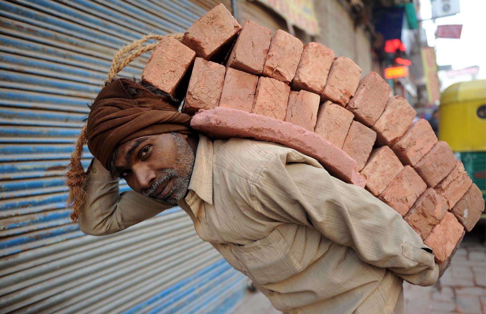 NICHT VERWENDEN Arbeiter mit Ziegeln in Neu Delhi