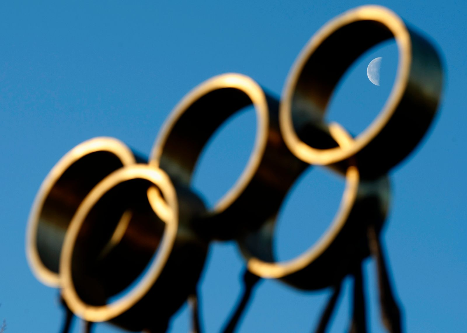 The moon is pictured through a sculpture in front of the IOC headquarters in Lausanne