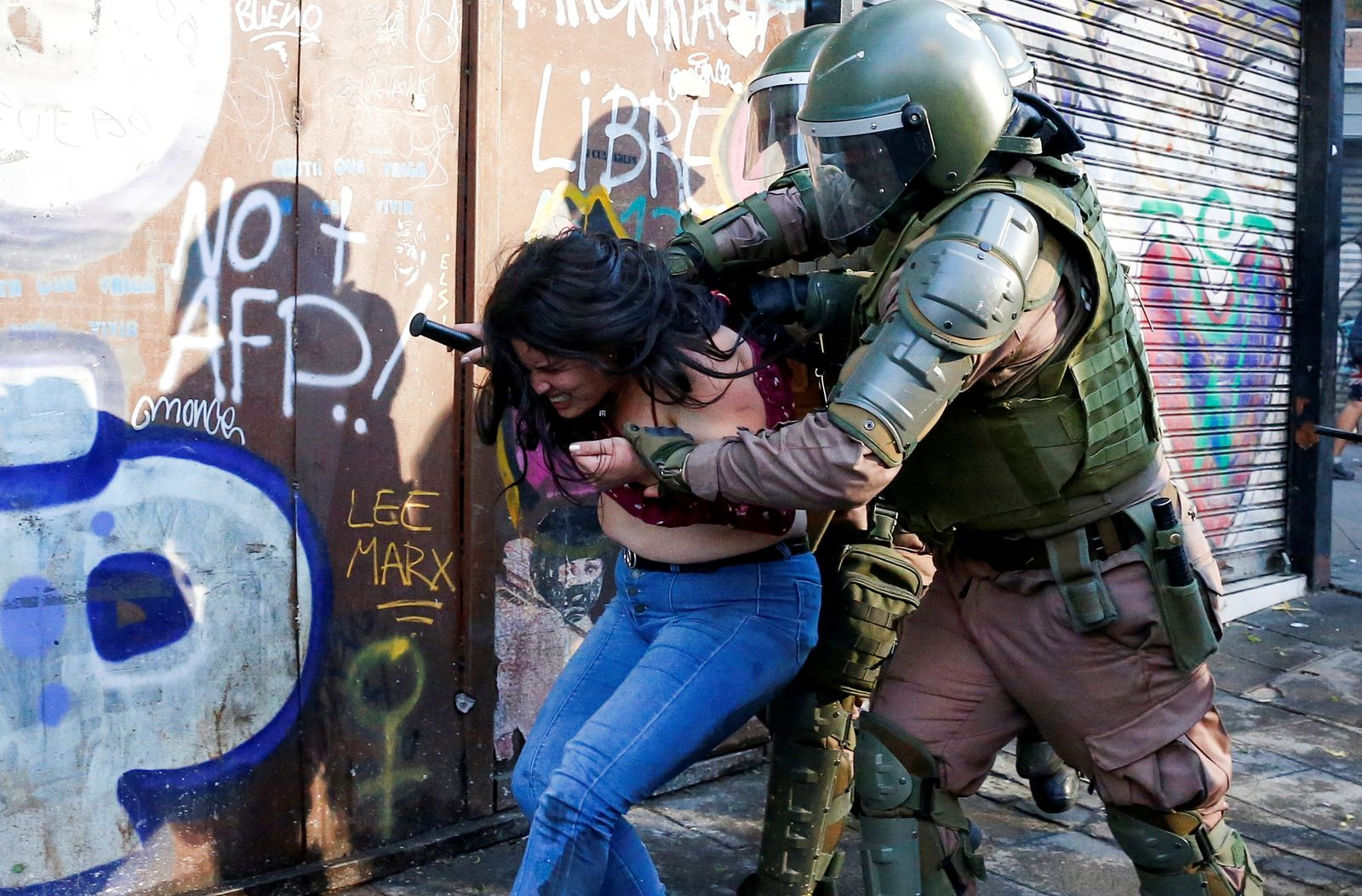 A demonstrator is detained by riot police during a protest against Chile's government in Valparaiso