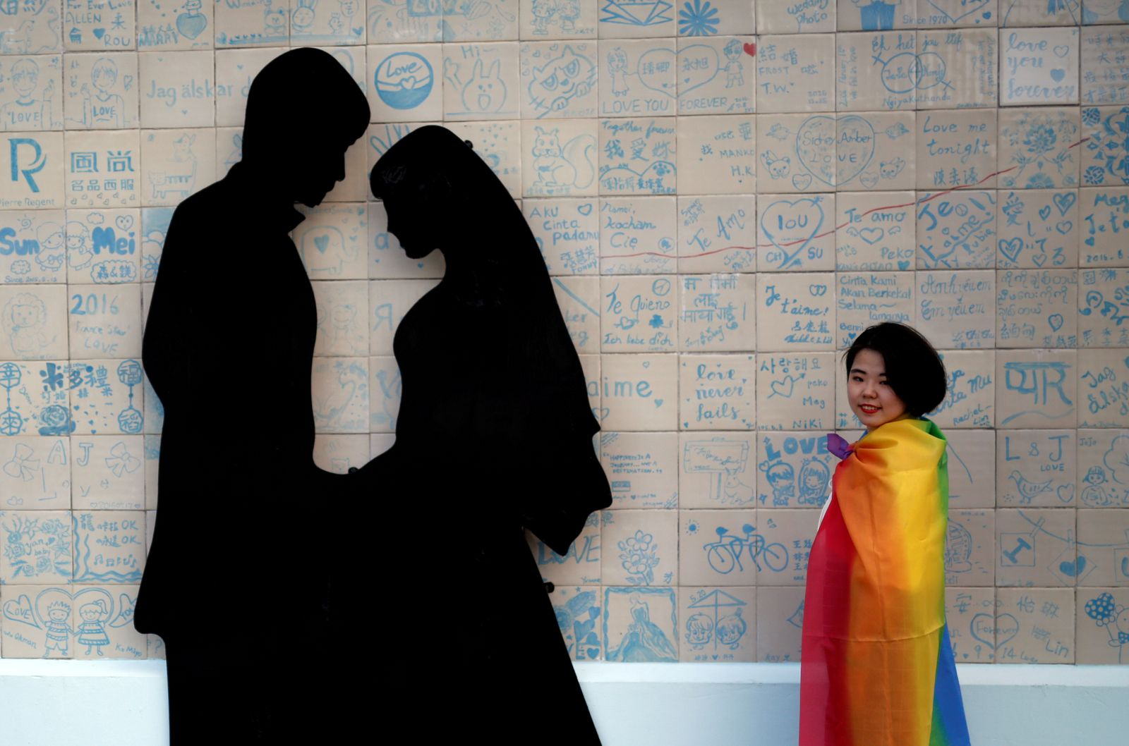 A participant poses next to a wedding studio during a LGBT pride parade to support same-sex marriage in Taipei