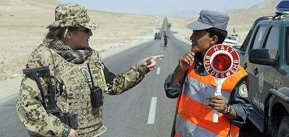 "A soldier of the German Bundeswehr Army trains an Afghani police officer in northern Afghanistan: ""Demands for an immediate withdrawal are irresponsible."""