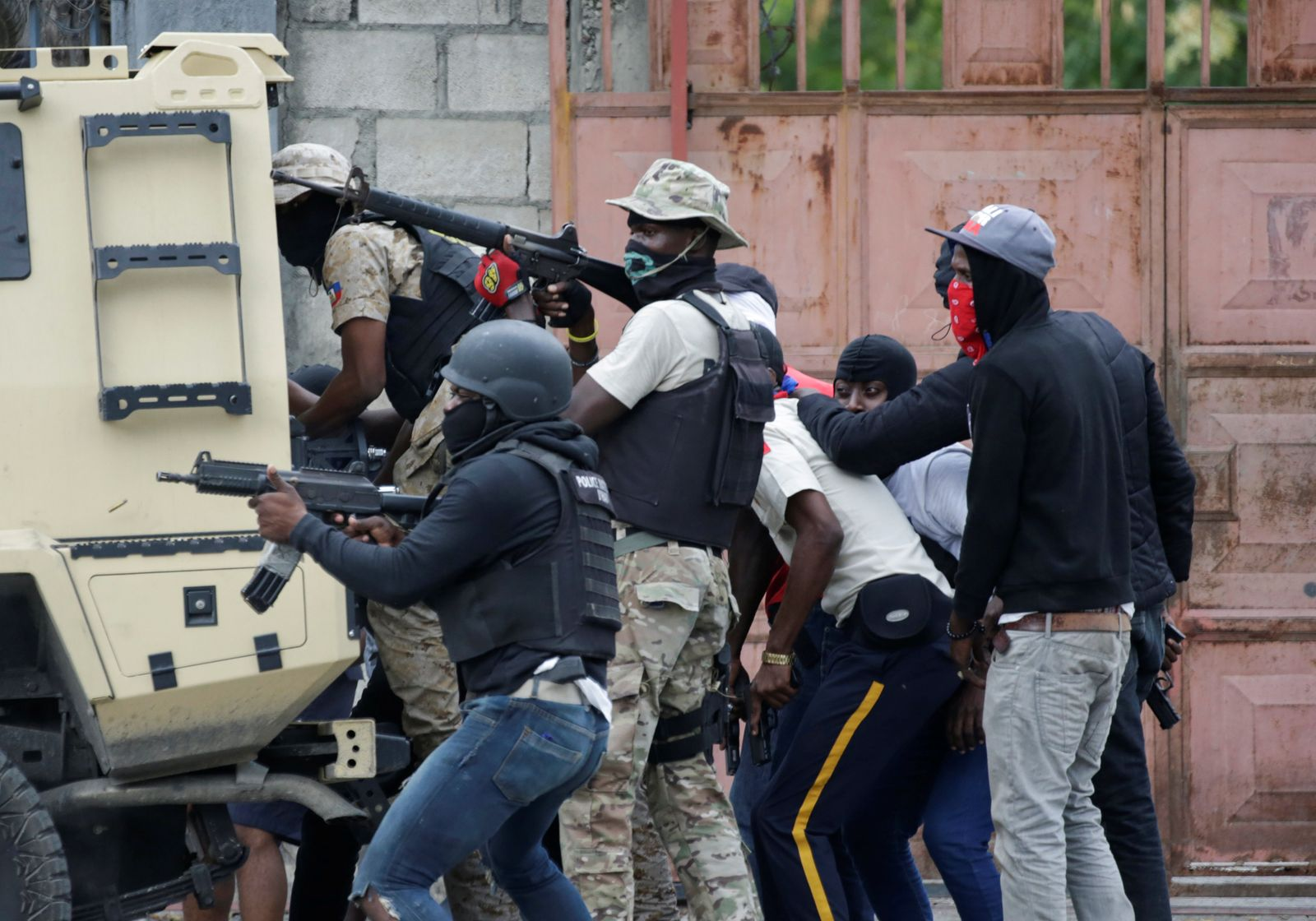 Protesters and police members take cover behind a police armoured vehicle during a shooting in Champ de Mars, Port-au-Prince