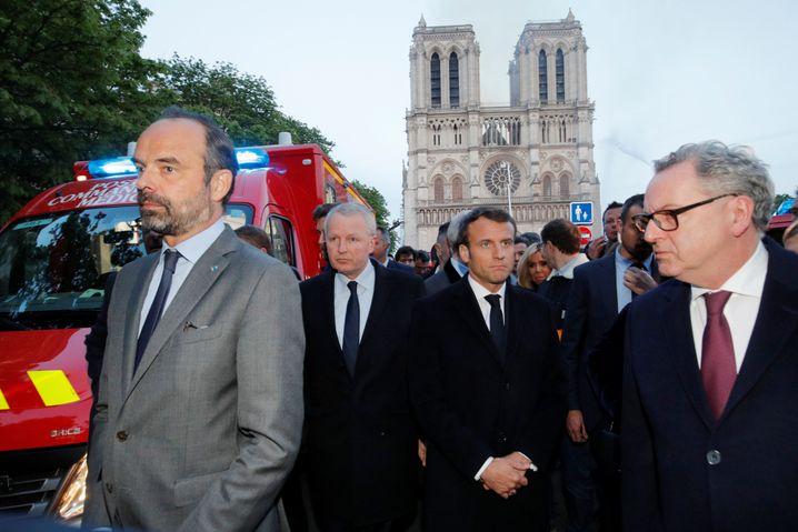 Emmanuel Macron (Mitte) vor der Kathedrale