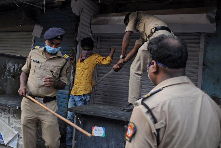 In Mumbai schlägt ein Polizist einen jungen Mann, der sich nicht an die Ausgangssperre hält