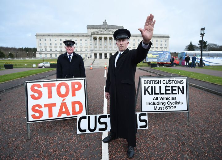 """Two men dressed as customs officers take part in a protest against Brexit in Belfast. A hard border, Gerry Adams says, is """"going to be totally and absolutely disastrous."""""""