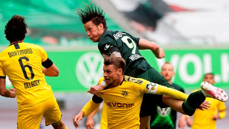 Lukasz Piszczek (M.) wehrt sich gegen Wolfsburg Wout Weghorst
